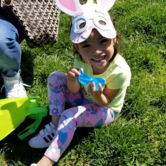 A little girl wearing a bunny mask hold an open Easter egg she found during the Beeping Egg Hunt event.