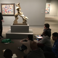 Participants listen to their teacher.  ID: Sitting in a semi-circle attentively listening during an art class.