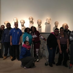 Participants grouped together for the picture.  ID: Standing in front of head sculptures.