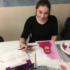 Participant smiles for the camera.  ID: She is holding a blush and is painting a self portrait.