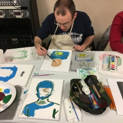 Participant painting a self portrait.  ID: Participant wearing glasses sits at a table with art supplies.