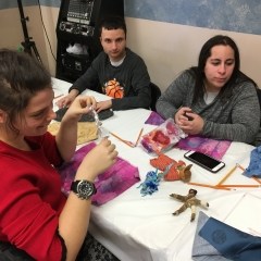 Participants working on an art project.  ID: Sitting around a table with art supplies.