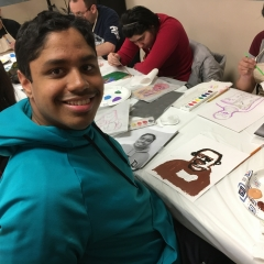 Participants working on their self portraits.  ID: In the center, a participant smiles for the camera.