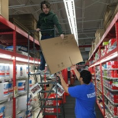 Participants work together to restock shelves with cardboard boxes.