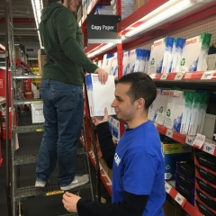 One participant passes printing paper to another participant on a ladder to restock higher shelves.
