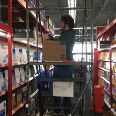 Participant stands on a ladder while restocking printing paper.