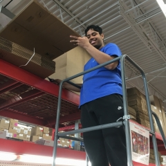 Participant puts away cardboard boxes while working at Staples.