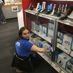 Participant cleaning a glass display while working at Staples.