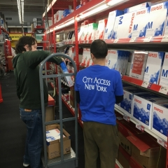 Participants work together to restock printing paper aisle at Staples.