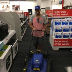 Participant vacuums an aisle while working at Staples.