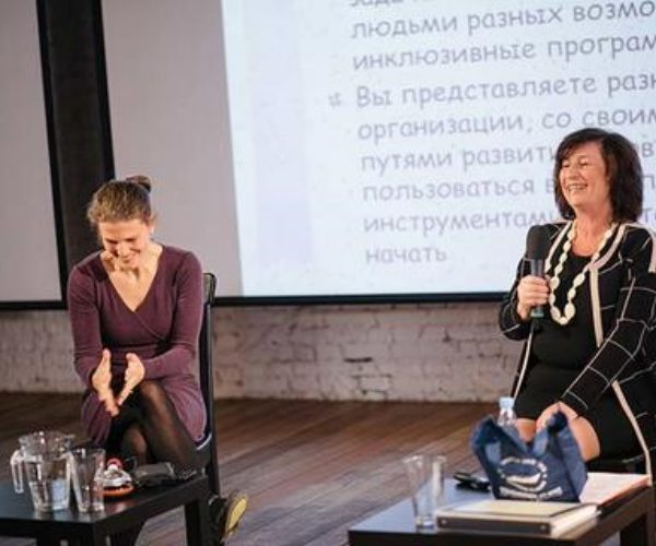 Two woman sitting down. One woman is holding a microphone