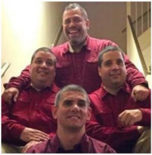 4 men sitting on stairs in red button downs